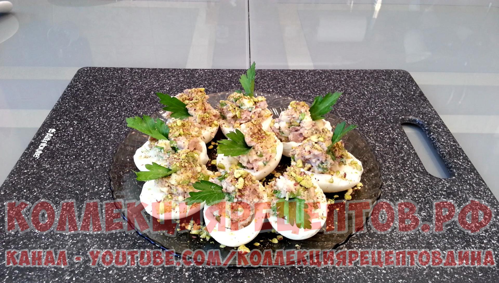 Нафаршированные яйца посыпаем сверху измельченными фисташками и украшаем листочками петрушки